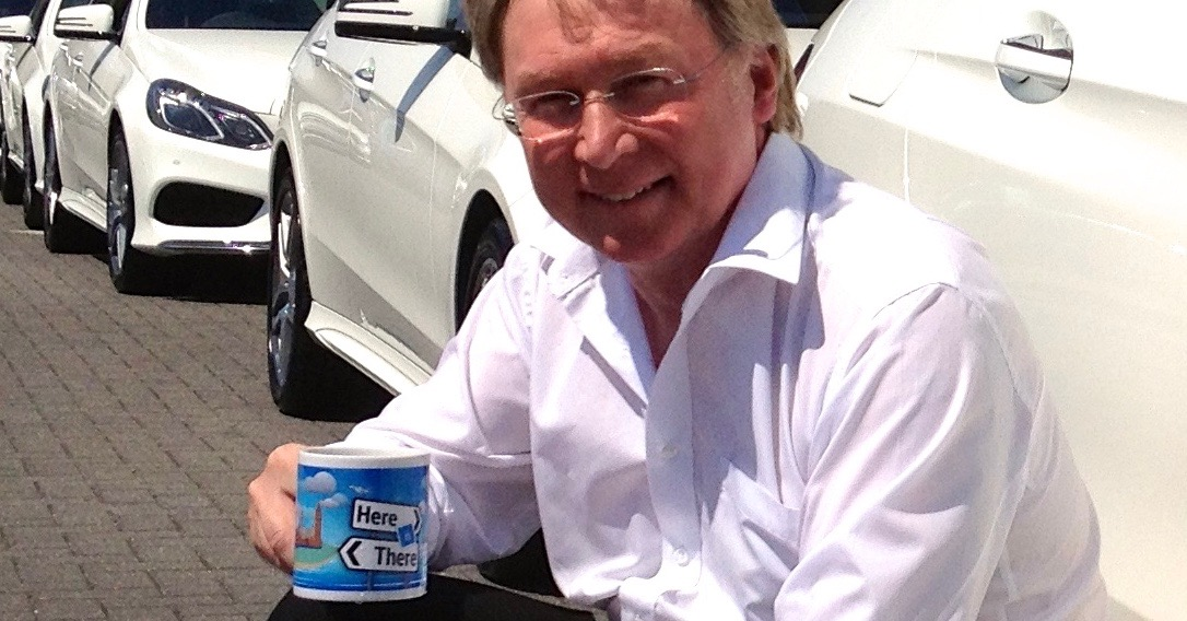 A photograph of Vince with a tea mug squatting in front of a row of white Mercedes-Benz E Class cars