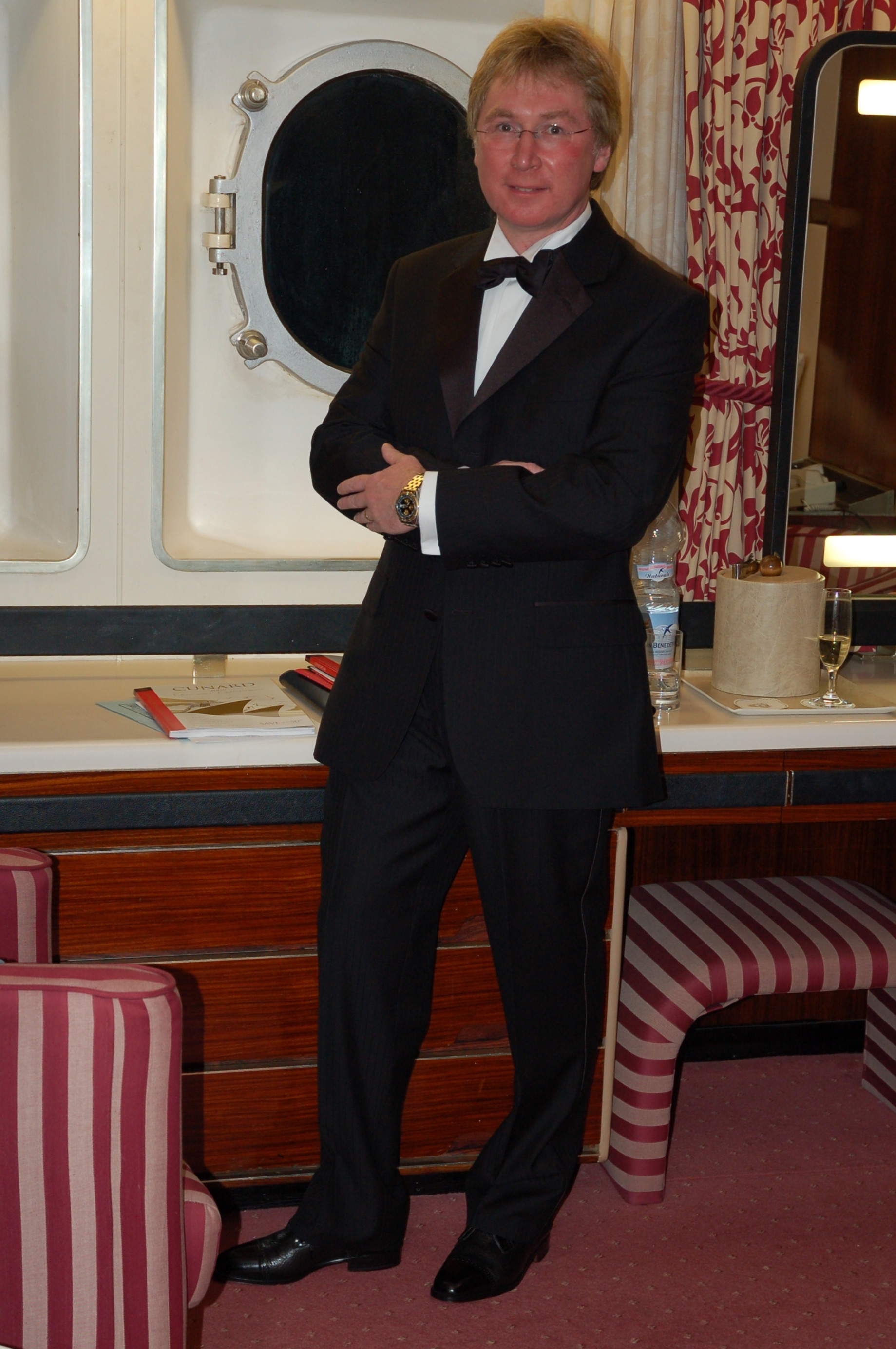 Vince stood, dresed in a classic Tuxedo, arms folded, in a ships cabin