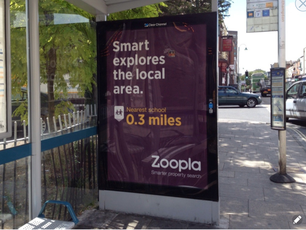 A large colourful advertising poster on a bus shelter for Zoopla saying 'Smart explares the local area' with a note pointing the distance to the nearest school